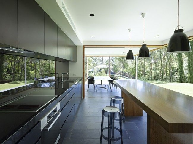 Fig Tree Pocket house.    The abundance of natural light in the kitchen area makes this space so inviting, which isn't always the case with  dark finishes. This is also accentuated by the mirror splash back.