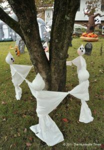 White Ghosts Surrounding Tree To Create Spooky Halloween