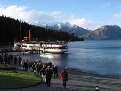 The photo of Michael Kemp shows the scene 'Disembarking at Walter Peak' during a trip on the TSS Earnslaw on Lake Wakatipu.