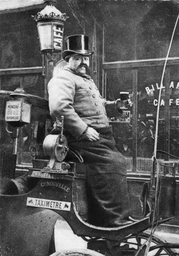 A Paris horse cab driver enjoying a glass of his favorite beverage. Note the early taximeter.