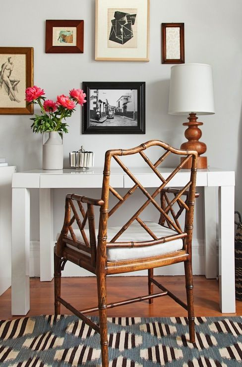 Eclectic style office with West Elm Parsons Desk paired with a chinoisserie chair. The table is topped with a vase of pink flowers and a modern turned wood table lamp. The wall above the desk features a fun collection of framed prints and art. The hardwood floors are layered with a blue, black and ivory vintage style rug.