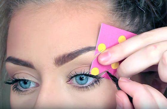 Chica delineando sus ojos usando una plantilla
