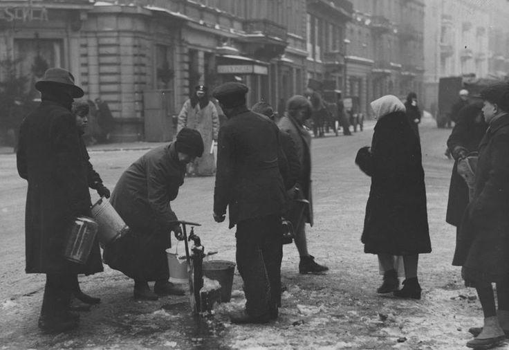 Ludzie nabierający wodę z hydrantu ulicznego, widok ulicy Szpitalnej od strony ulicy Chmielnej. fot. 1929r., źr. Narodowe Archiwum Cyfrowe.