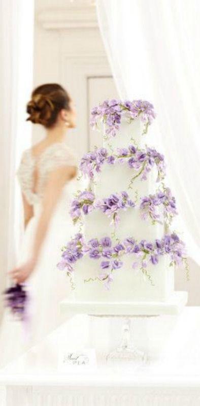 classic white wedding cake with purple cascading wisteria