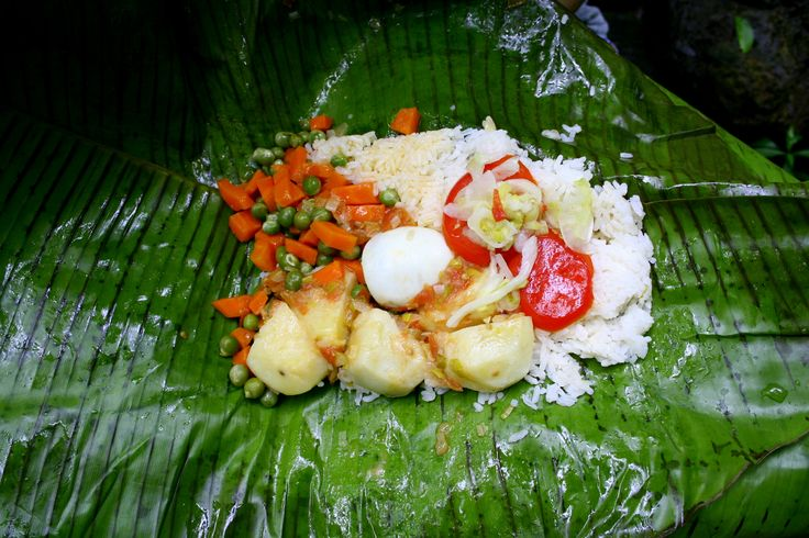 Typical Colombian Food: A Fiambre comes with different ingredients, usually rice, potatoes, veggies, chorizo, chicharron and ground Beef topped with an egg. Later it is wrapped up in a banana leaf. The perfect lunch for a day out hiking! #Food #typical #colombia #travelandmakeadifference #bananaleaf