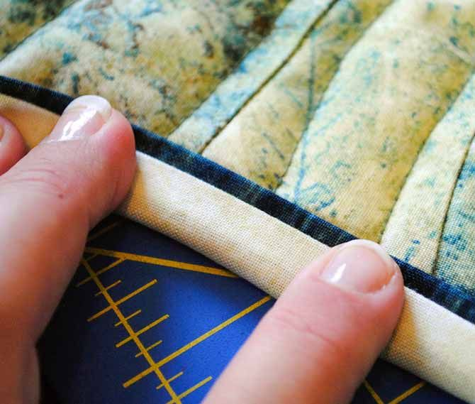 The binding is flipped around to the front of the quilt and the flange of the accent color is exposed