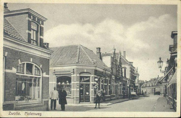 Gezicht in de Molenweg vanuit het oosten op de kruising met de Groenestraat, ca. 1925. Vanaf links Molenweg 52, slagerij A.J. de Bondt, met vlees in de etalage; op de hoek met de Groenestraat Molenweg 50, de winkel in huishoudelijke artikelen, sportvisserij-artikelen, galanterieën, lampen enz van L. Boetes. Bijzonder fraai zijn de gevels van Molenweg 44 en 46. De foto dateert van na 1923 toen de gevel van Molenweg 46 mismaakt werd.