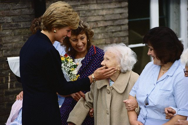 Princess Diana Visiting Lord Cage Center  Princess Diana touches the cheek of an elderly woman at the Lord Cage Center in Newham.  Image: © Tim Graham/CORBIS  Photographer:	Tim Graham  Date Photographed:	September 18, 1990  Location Information:	Newham, London, England, UK