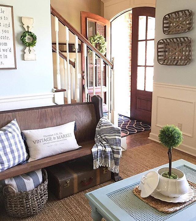 I love the front door, the brown baskets on the blue wall, the bench seating with a basket and a suitcase underneath.