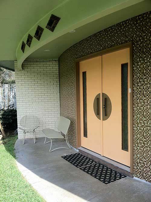mid century front porch. round walls, double front doors w/sidelites. brass escutcheons. exterior tile work.