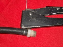 Pop Riveter Clamping Tool - Homemade clamping tool adapted from a manual pop riveter. A looped piece of wire, intended as a hose clamp, is tensioned and twisted by the riveter, with the excess cut off and folded over.