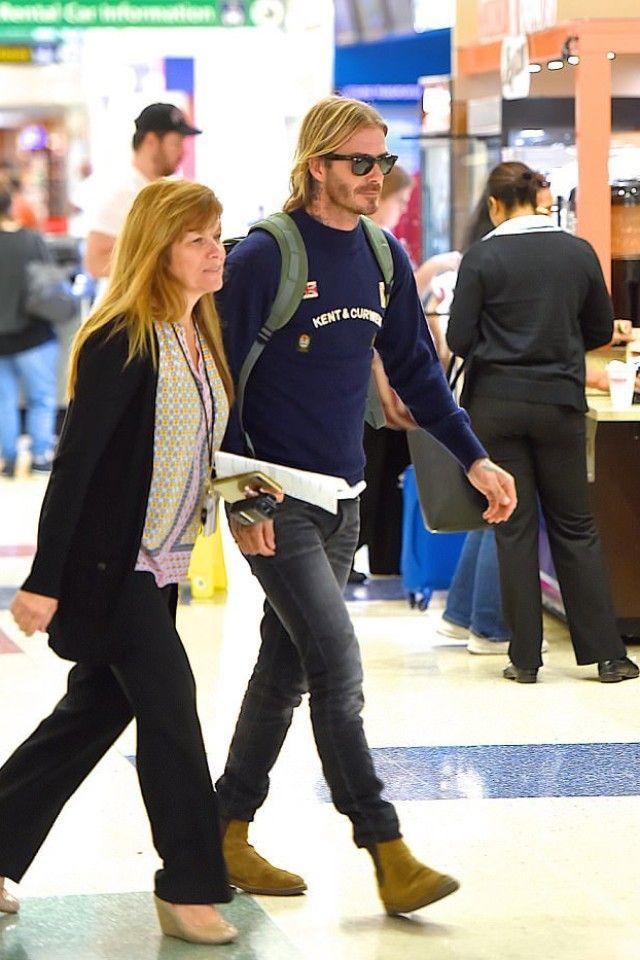 David Beckham wearing  Saint Laurent Wyatt 30 Jodhpur Boot in Cigar Suede, Kent And Curwen Badge Patch Sweater, Ray-Ban Wayfarer Sunglasses, Saint Laurent Skinny-Fit 15cm Hem Stretch-Denim Jeans