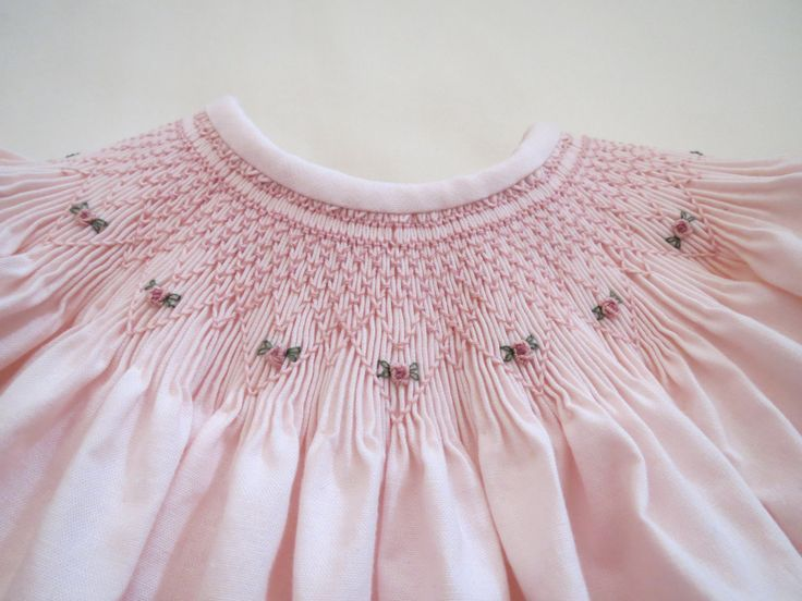 With its lovely hand smocked and embroidered round yoke and shadow work embroidery with bullion rose bud detail above the hem, and adorable short puffed sleeves edged with delicate smocking, this dress is just blooming with exquisite detail. Tiny natural shell buttons fasten up the back. Made of 100% cotton, high quality, pre shrunk, pale pink cotton fabric. And sewn with quality and extra special care for each detail just for that dear little girl in your life! Machine wash. Tumble dry…