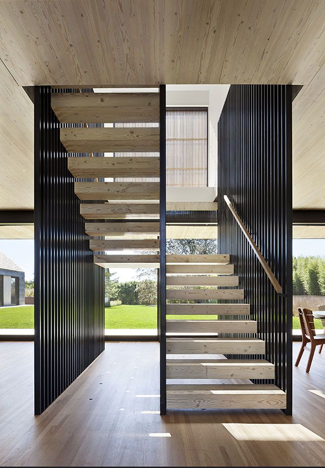 The thick stair treads are constructed of the same rich material, linking the house with its natural surroundings