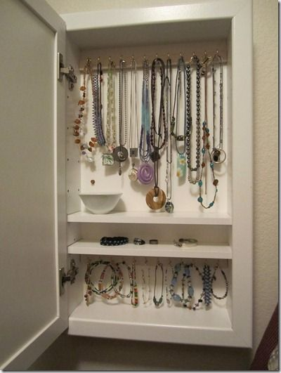 Turn a medicine cabinet into a wall-mounted jewelry box.  It only takes a few minutes, and used medicine cabinets are inexpensive and easy to find.