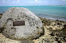 """The story is that the commander of the Japanese garrison ordered  the execution of 98 captured Americans.  One escaped and carved """"98 US PW 5-10-43"""" on this coral rock.  It's still there."""