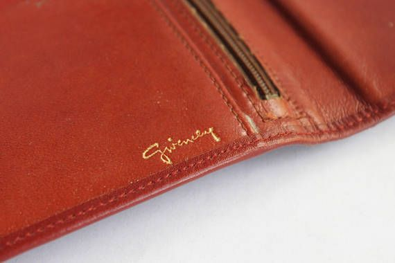 Beautiful Vintage 80s Givenchy Designer Brown Leather Wallet  This rich brown leather wallet is a classic piece of Vintage Givenchy! It has a snap closure along with a clasp change pocket on the outside of the wallet. There is another zipper pocket on the interior and several credit card slots. Please note: As with many vintage pieces, there are some slight flaws with this wallet. The interior has some light scratching on the leather. The outside is in almost pristine condition besides two…