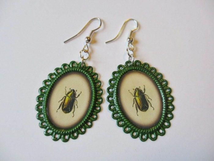 Earrings made of ornate oval-shaped frames and pictures of bugs. Minka / www.madeby.fi