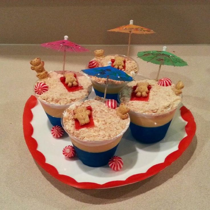 Teddy Graham Beach Dessert Cups: Ingredients: Makes 4 [ ] 1 Box Berry Blue Jello [ ] 1 Box Cheesecake Pudding [ ] Nilla Wafers [ ] Teddy Grahams [ ] Fruit by the foot [ ] Round peppermints [ ] Toothpick Umbrella Steps : I first made the jello (ocean) and let it sit in the fridge for a few hours,…
