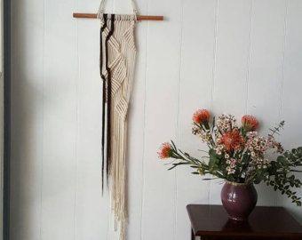 Un design minimale realizzato con corda di cotone 100%.  #Dimensions #  Lunghezza di Macrame - 128cm Larghezza di macrame - 27,5 cm Larghezza del supporto pole - 40,5 cm