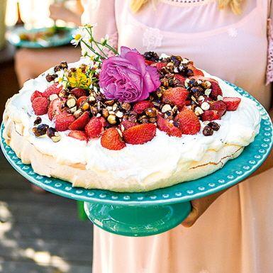Pavlova är en klassisk marängtårta som går att fylla med det man gillar allra bäst. Här toppas den frasiga, men ändå sötsega, marängbottnen med en frisk rabarbercurd, söta jordgubbar och hasselnötter som rostats med honung. Somrigt värre – och riktigt gott!