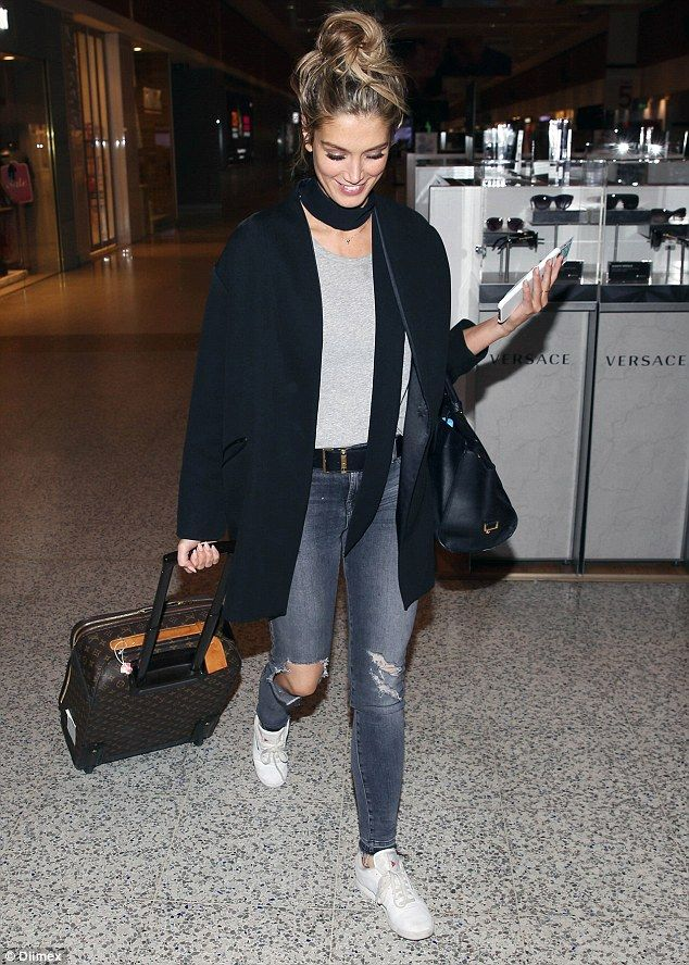 Airport style: Delta Goodrem wheeled a designer suitcase behind her as she made her way th...
