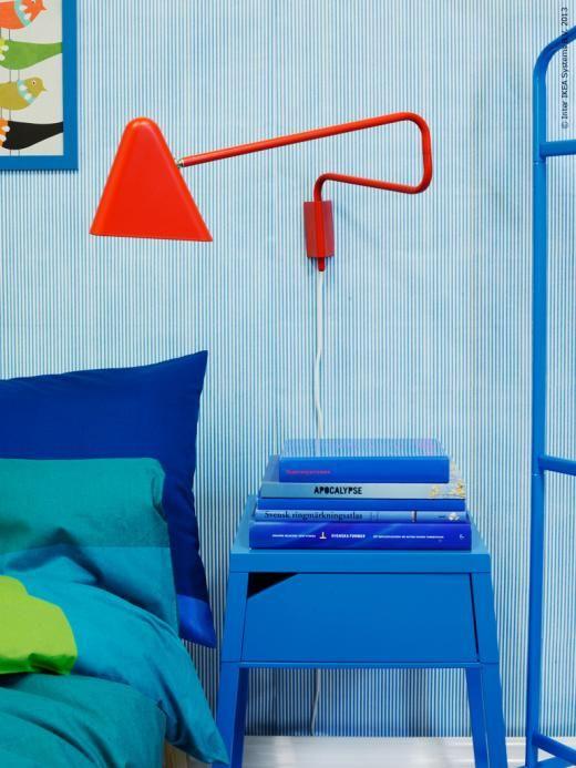 Sovrum i blått och rött: sängbordet SELJE med stadiga ben och en rymlig låda, vägglampa IKEA PS 2012, BRUNKRISSLA påslakan.