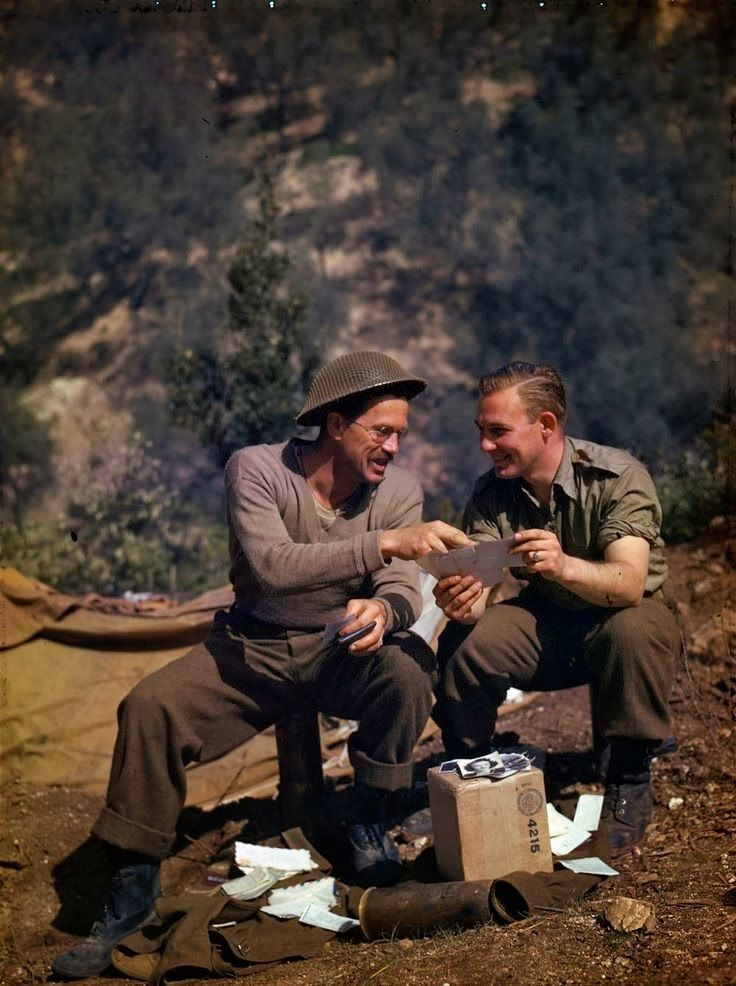 Canadian gunners looking at photographs and letters on a mountainside in Italy.