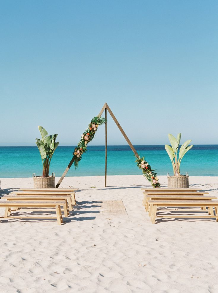 Wild Wolf Collective styled a tropical luxe beach wedding in Bunker Bay using our timber tripod arbour, tropical plants and a gorgeous white vintage peacock chair. We call it tropical meets romance.