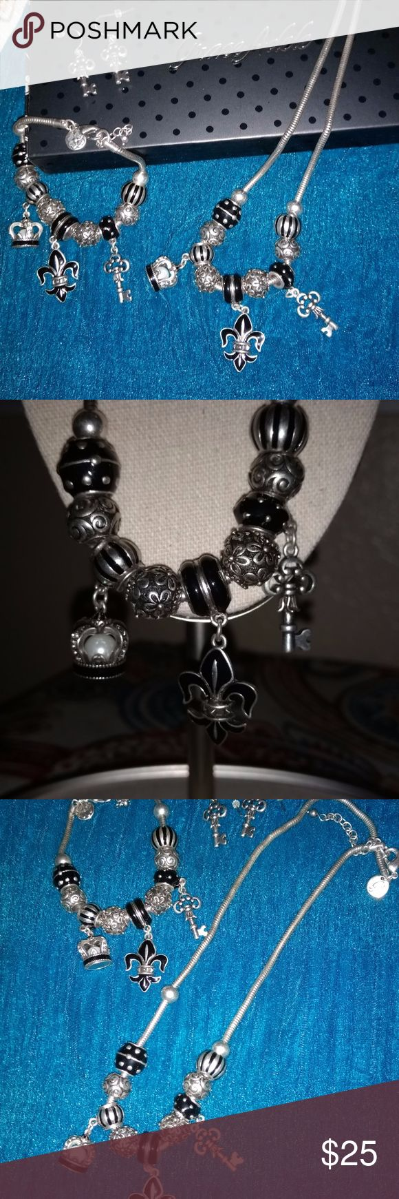 Grace Adele 3 Piece Set Grace Adele 3 piece jewelry set.  Necklace, bracelet and earrings.  Fleur de lis, crown and key charms with coordinating beads.  Black and Silver,  Earrings are keys.  Never worn. Grace Adele Jewelry Necklaces