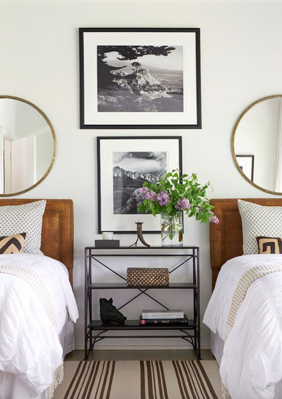This room is very nicely styled. Two gorgeous single beds, black and white pictures, neutral colors with a splash of green. Very nice!   Andrew Brown Interiors