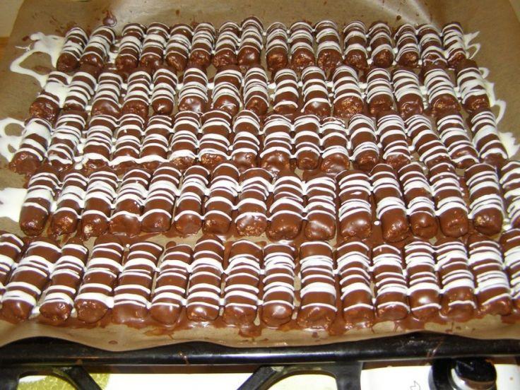Domácí mini Bounty tyčinky, krok 3: Nakonec nahřejeme ve vodní lázni sáček s bílou polevou, ustříhneme roh sáčku a přes válečky uděláme bílou polevou linky. Necháme ztuhnout. Naskládáme do krabice  a skladujeme v chladu. (Mívám cukroví plnej balkón ;-) )