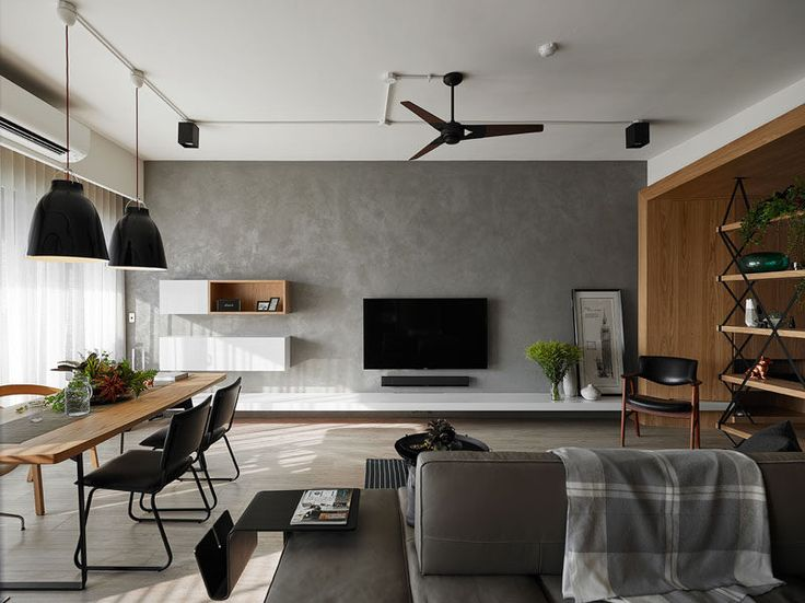 This grey feature wall in an apartment is home to the television and additional floating storage.