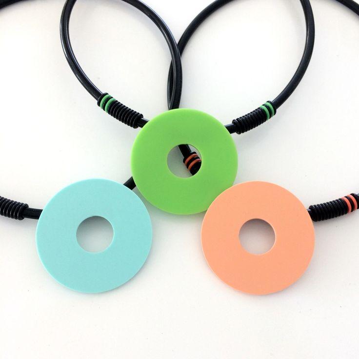 Broscher av plexiglas på gummilänk med o-ringar. Brooches made of plexiglass on rubber cord with o-rings