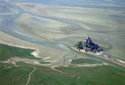 E' uno dei luoghi più iconici del mondo, un isolotto tidale situato presso la costa settentrionale della Francia, dove sfocia il fiume Couesnon. Per via del fenomeno delle maree è il sito turistico più frequentato della Normandia e uno dei primi dell'intera Francia, con circa 3.200.000 visitatori ogni anno. La baia in cui sorge l'isolotto roccioso è soggetta al fenomeno delle sabbie mobili