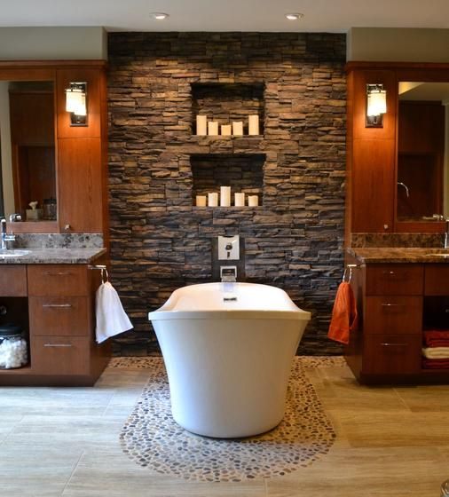 rustic master bath with dark stacked stone candle wall, white freestanding bathtub, wood cabinets and vanities. Sconces, orchids, tile floor and pebble floor
