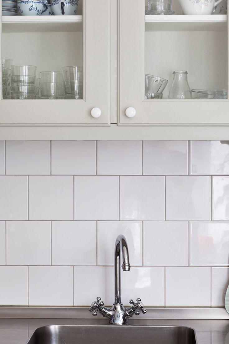 Måttbyggt mindre kök med knoppar och handtag i förnicklad mässing. Köket är målat med linoljefärg i kulören Vit Gräddton och kaklet på väggen är Field Tiles i Brilliant White med rundad kant vid avsluten.