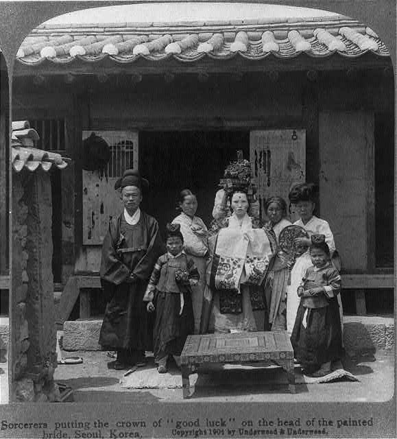 """Sorcerers putting the crown of """"good luck"""" on the head of the painted bride, Seoul, Korea. c. 1904"""