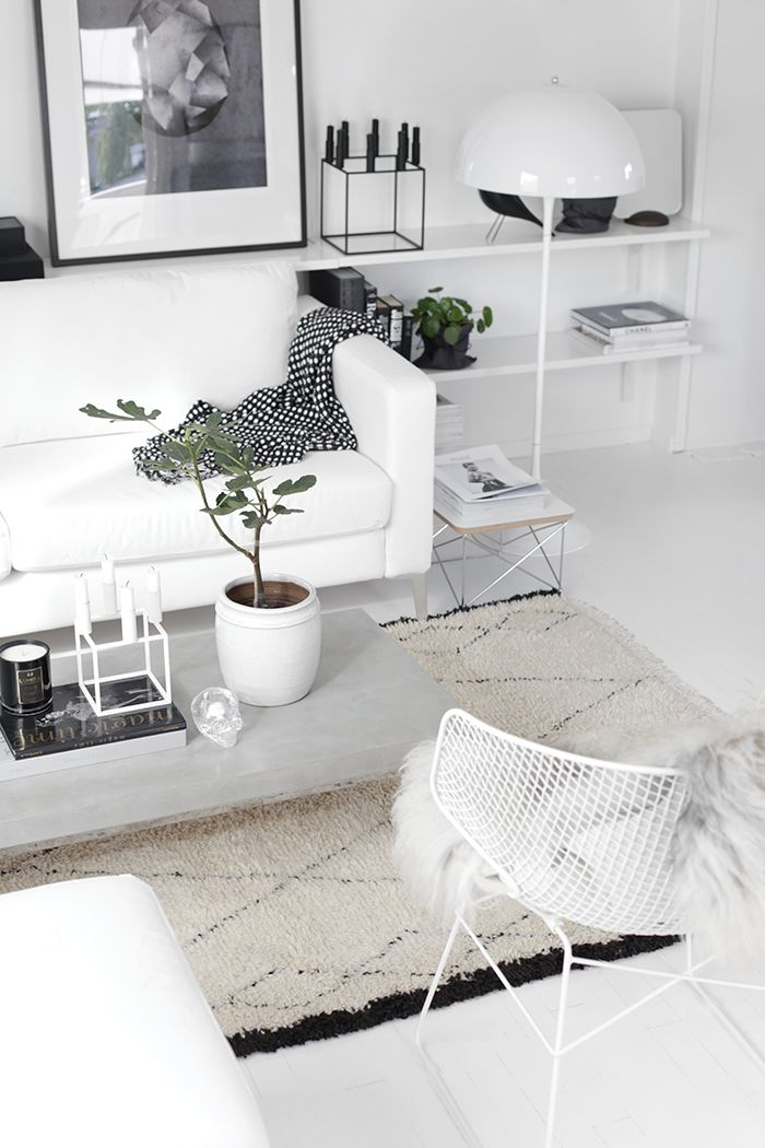 White living room with Kubus candle holders from by Lassen and Panthella floor light from Louis Poulsen. Via Stylizimo. Photo by Nina Holst.