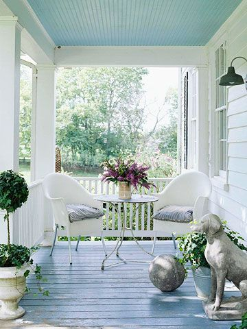 White plastic Philippe Starck chairs feel right at home on a country-style front porch with their blue-ticking cushions. Light blue paint on the ceiling gives the sense that you're always sitting under a clear blue sky. Antique treasures like the stone guard dog and ball make their way onto the porch, bringing the home's eclectic style outdoors./