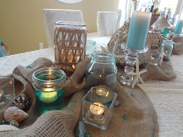Beach themed centerpiece, burlap table runner with pretty blue candles....this site did not lead to anything else with beach theme,  but I like this table setting (PD)