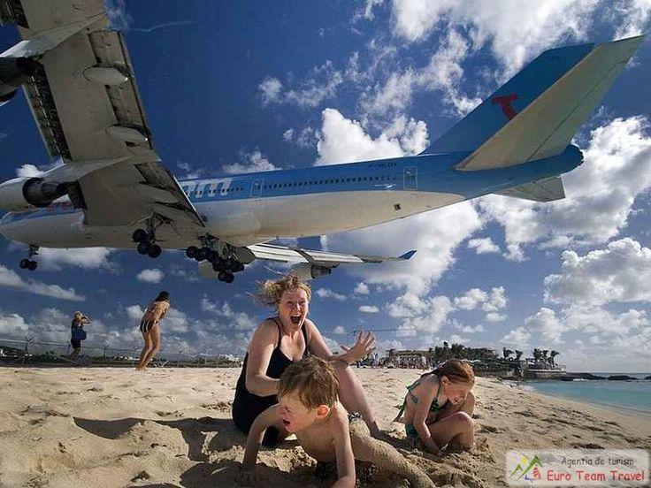 Zbor extrem si senzatii tari pe plaja din Maho Beach, Saint Martin Maho Beach nu este o plaja impresionanta la prima vedere. Este ingusta si destul de mica, incadrata de hoteluri. Insa nisipul este fin, apa de un turcoaz ideal, iar ceea ce o face cu adevarat unica in lume este pista de aterizare a aeroportului Princess Juliana. Avioanele trec fix deasupra plajei, la nu mai mult de 10-20 de metri, si sunt un adevarat paradis pentru cei pasionati de aviatie.