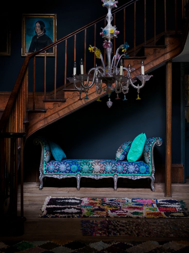 The Fontaine day bed in Butterfly Wheel ombre is positioned under a wooden staircase and colourful Venetian chandelier. Introducing Matthew Williamson's first ever bespoke furniture collection. Created in collaboration with Nottingham-based sofa manufacturer Duresta, the designs comprise five upholstery ranges and unique occasional.