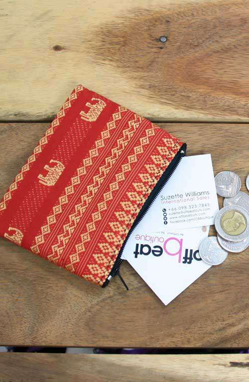 A cute little red coin purse with gold elephant print handmade in Thailand.