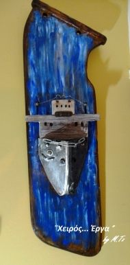 Old piece of fishing boat's rudder painted with oil paint . The bow is made of handcarved metal. More info: www.artsandcrafts.gr