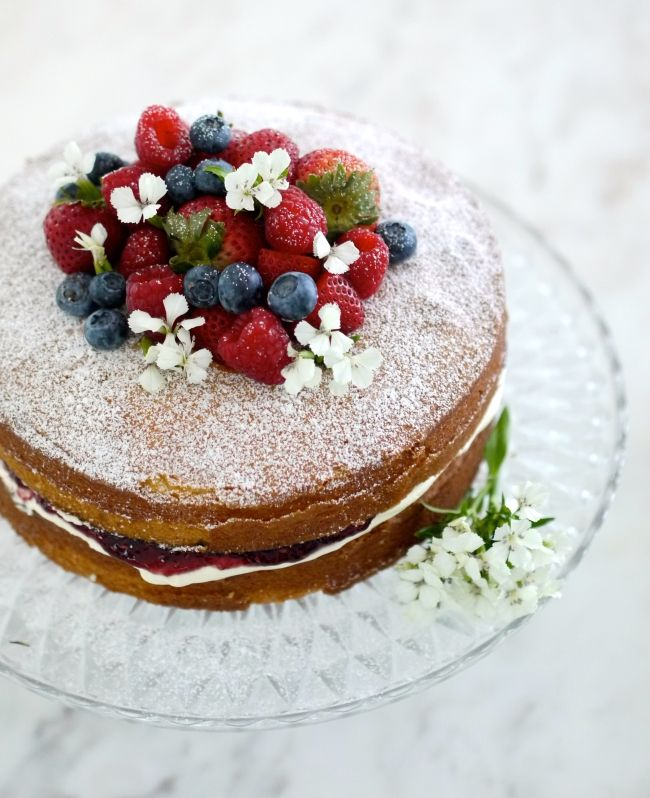 Victoria sponge simply decorated with berries and a few sprigs of flowers.