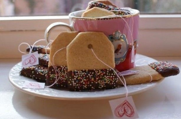 Eetbare theezakjes! Leuk idee van ze . nl Knip uit een vel wit papier een sjabloon in de vorm van een theezakje. Maak dan zanddeeg. nijd met behulp van de sjabloon de koekjes uit het deeg en leg deze op een ingevette bakplaat. Druk aan de bovenkant met een rietje een rondje voor het touwtje. Als ze klaar zijn, in gesmolten chocola dopen, evt spikkels erop en klaar is kees!