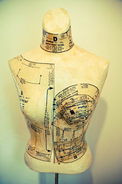 Decoupage dress patterns onto dress form. I like the asymmetry and thought put into matching pattern to part of torso.