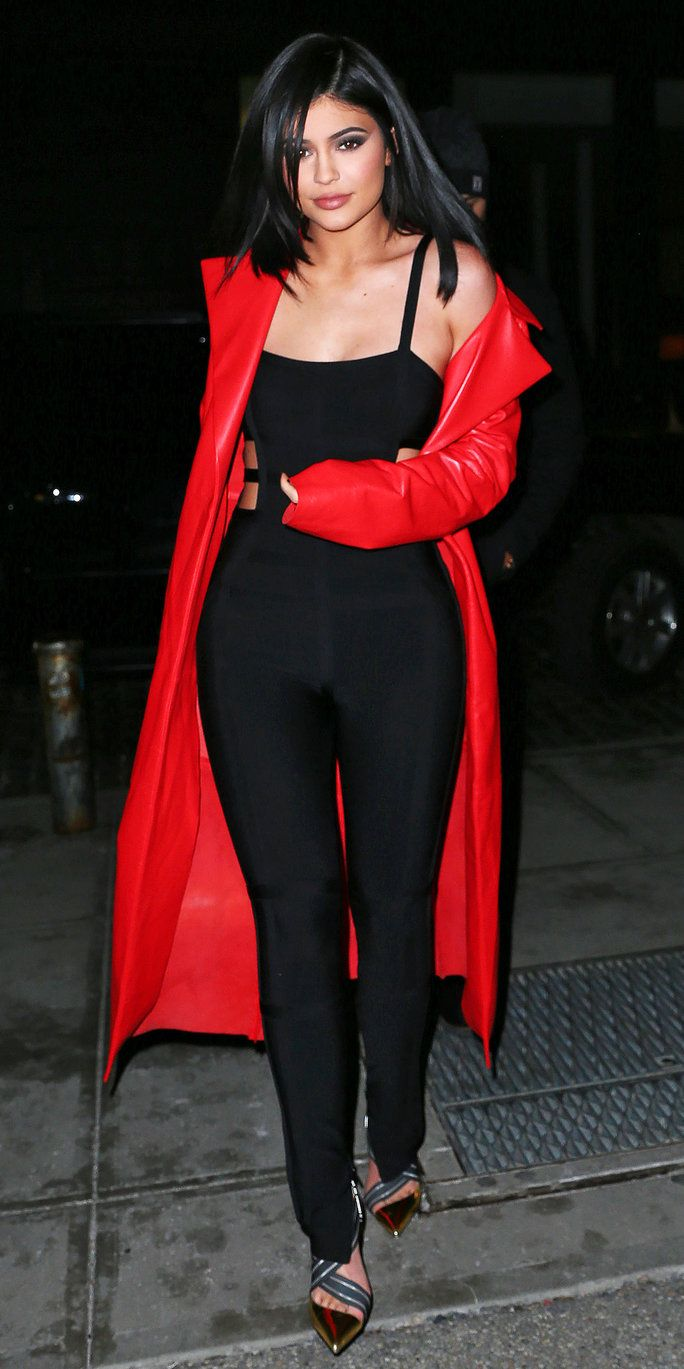 Kylie Jenner makes a street style statement in a red coat and all-black outfit.