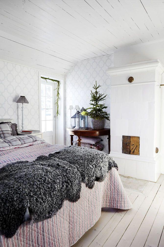 I sovrummet råder en ombonad julkänsla som förstärks av många textilier där flera lager sänglinne, överkast och fårskinn går ton i ton. Den glasade balkongdörren ger ett härligt ljusinsläpp.